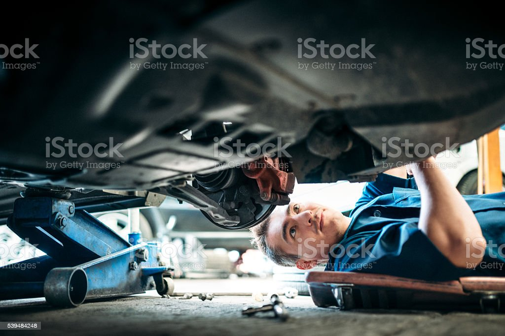 Car Mechanic Working Under Vehicle stock photo