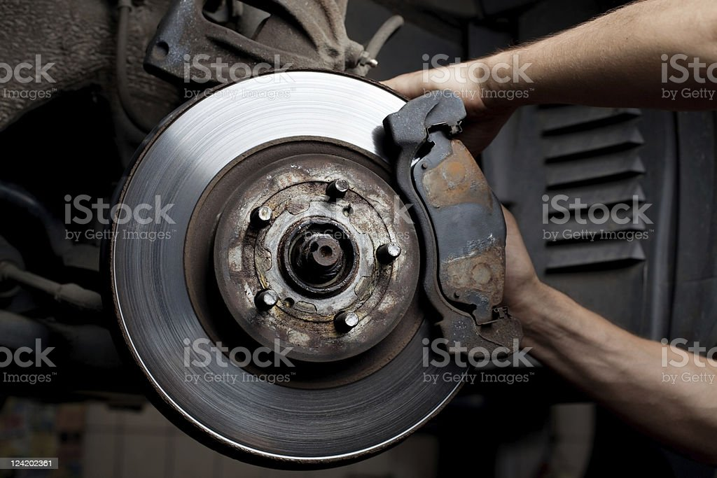Car mechanic's hands repairing a car's brake pads royalty-free stock photo