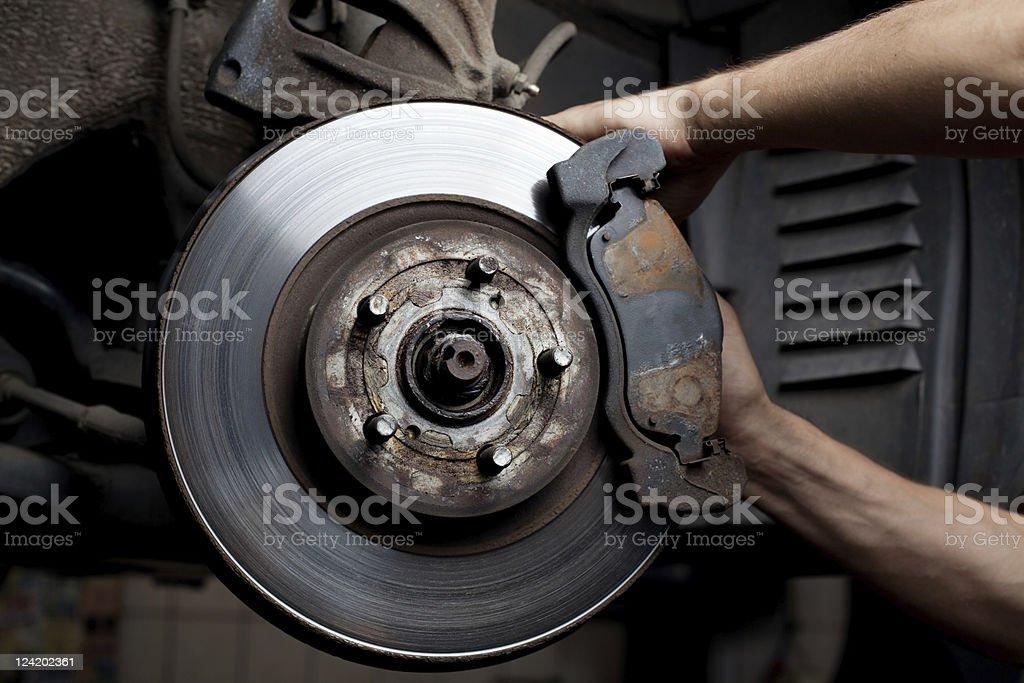 Car mechanic's hands repairing a car's brake pads stock photo