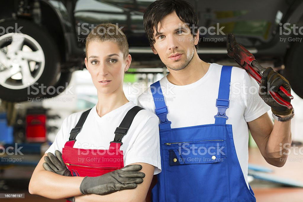 Car mechanics male and female in front of auto royalty-free stock photo