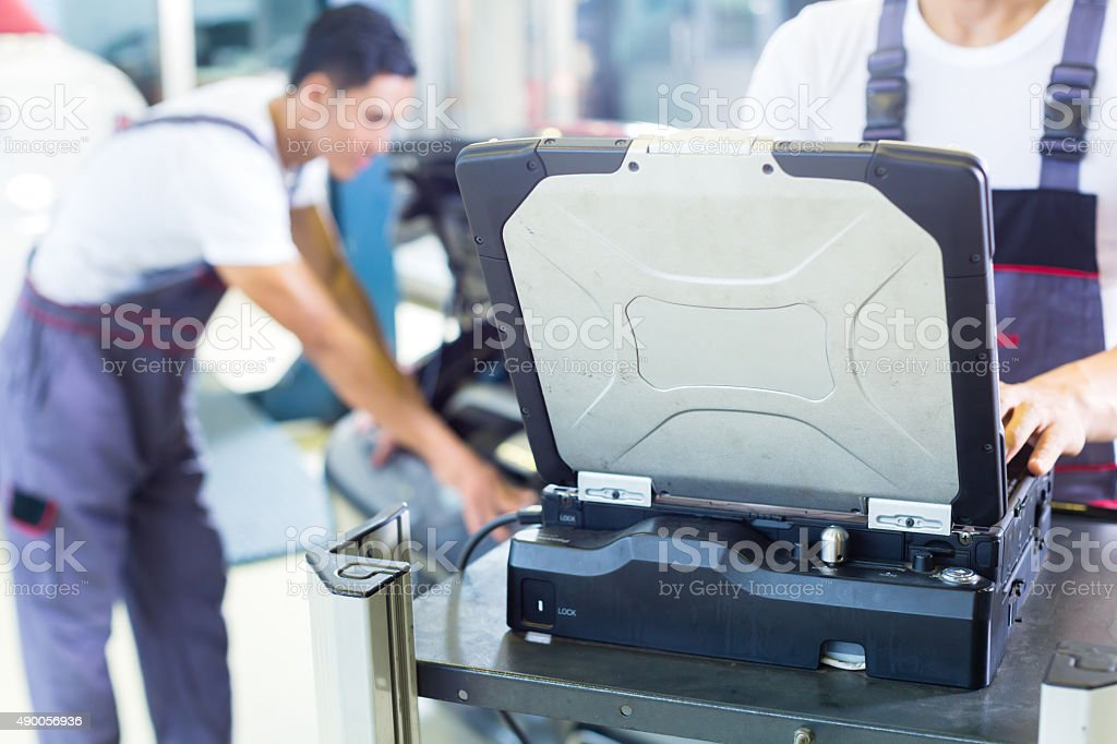 Car mechanics with diagnosis tool in Asian auto workshop stock photo