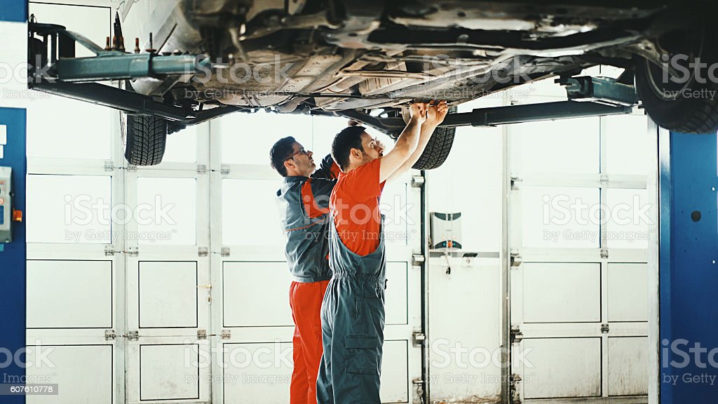 Car mechanics workin on low section of a sedan vehicle. stock photo