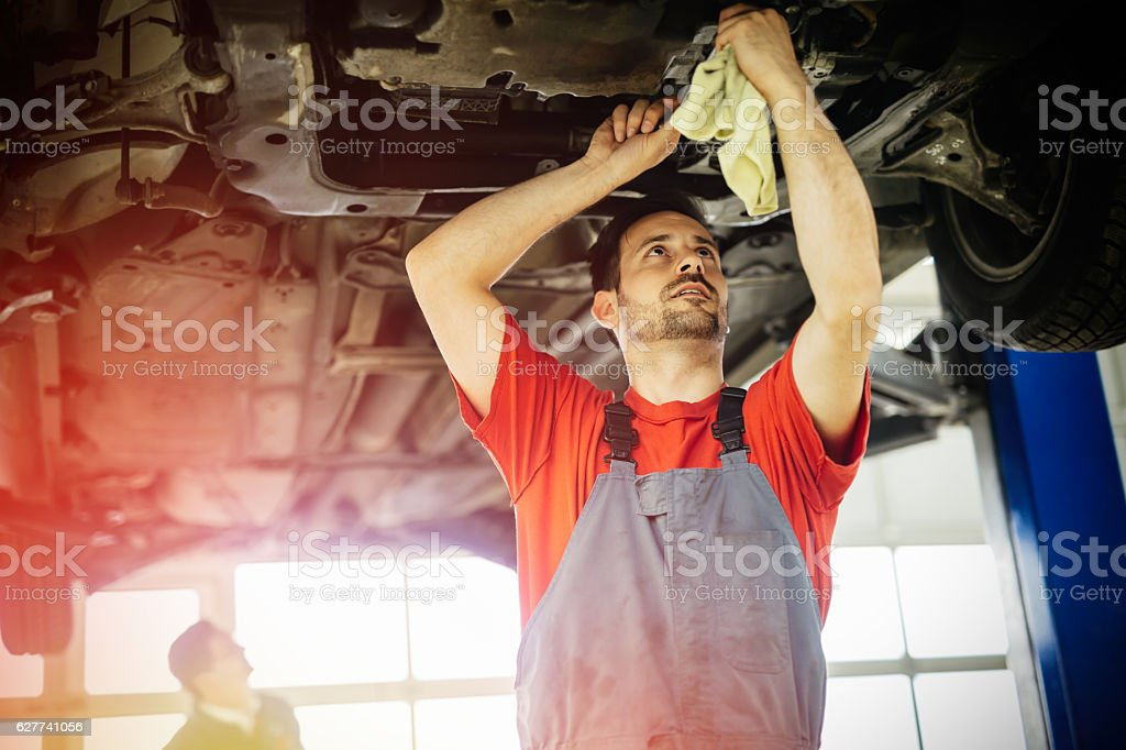 Car mechanics working and maintaining car stock photo