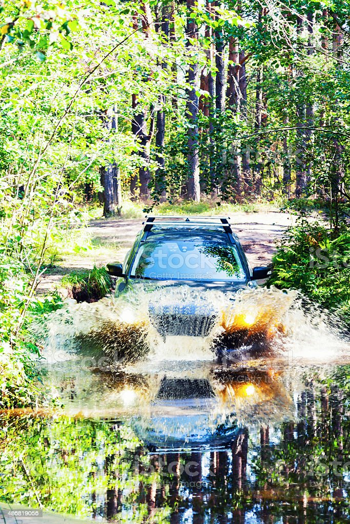 Car moving through a large puddle in the woods stock photo