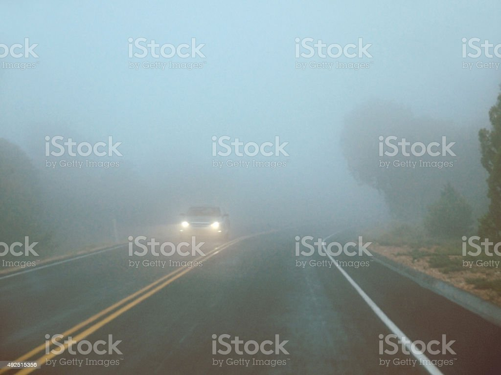 Car on a foggy road stock photo