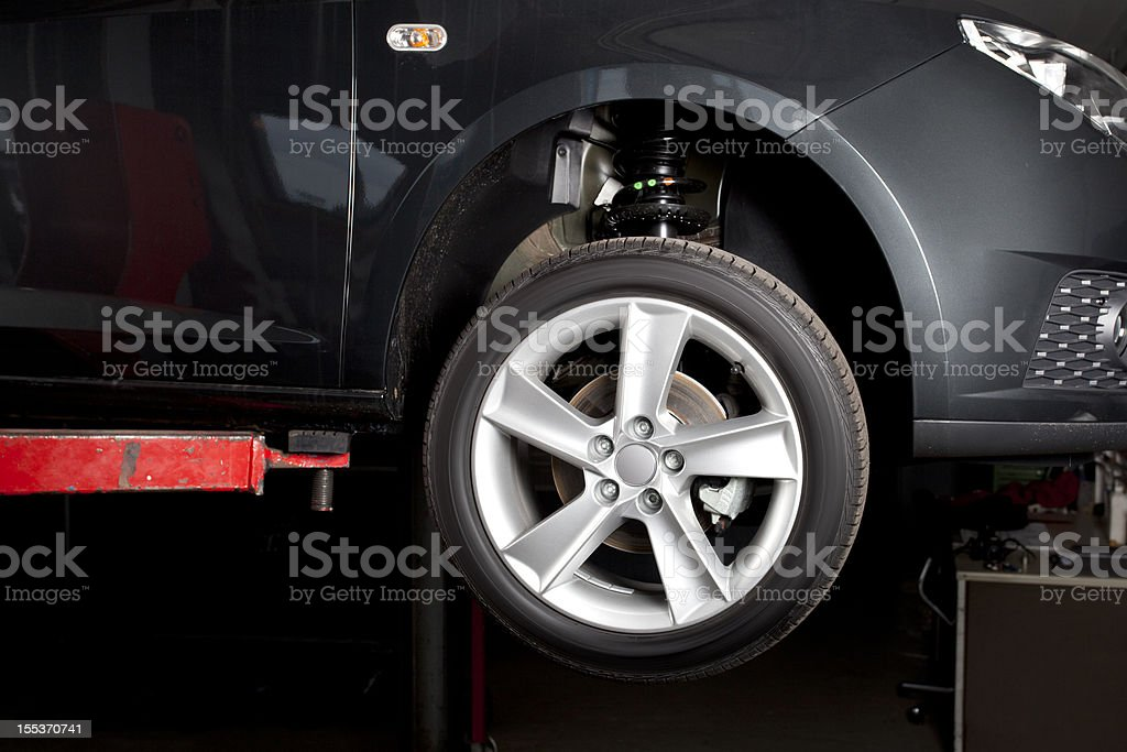 Car on a lift - ready for tire change stock photo