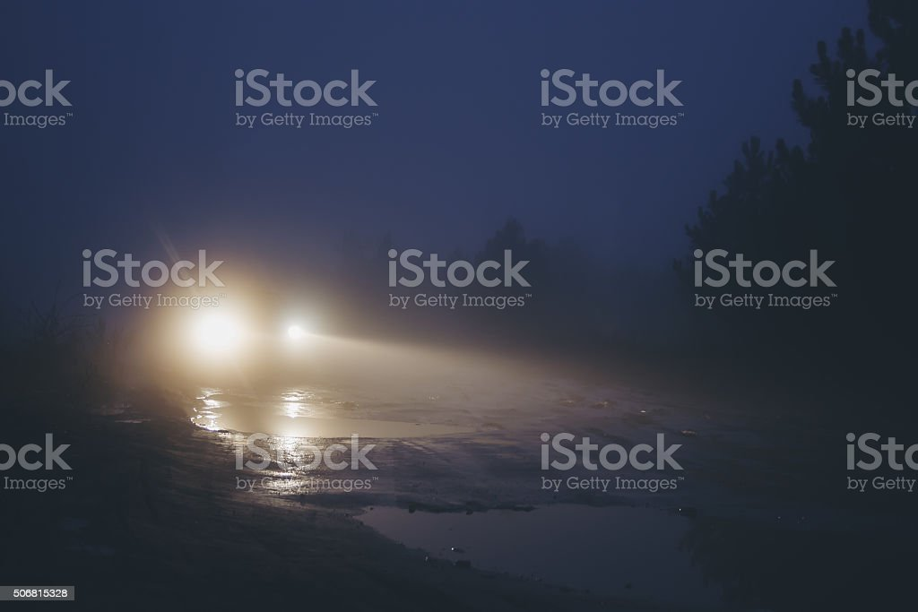 Car on dirty road in strong haze fog at twilight stock photo