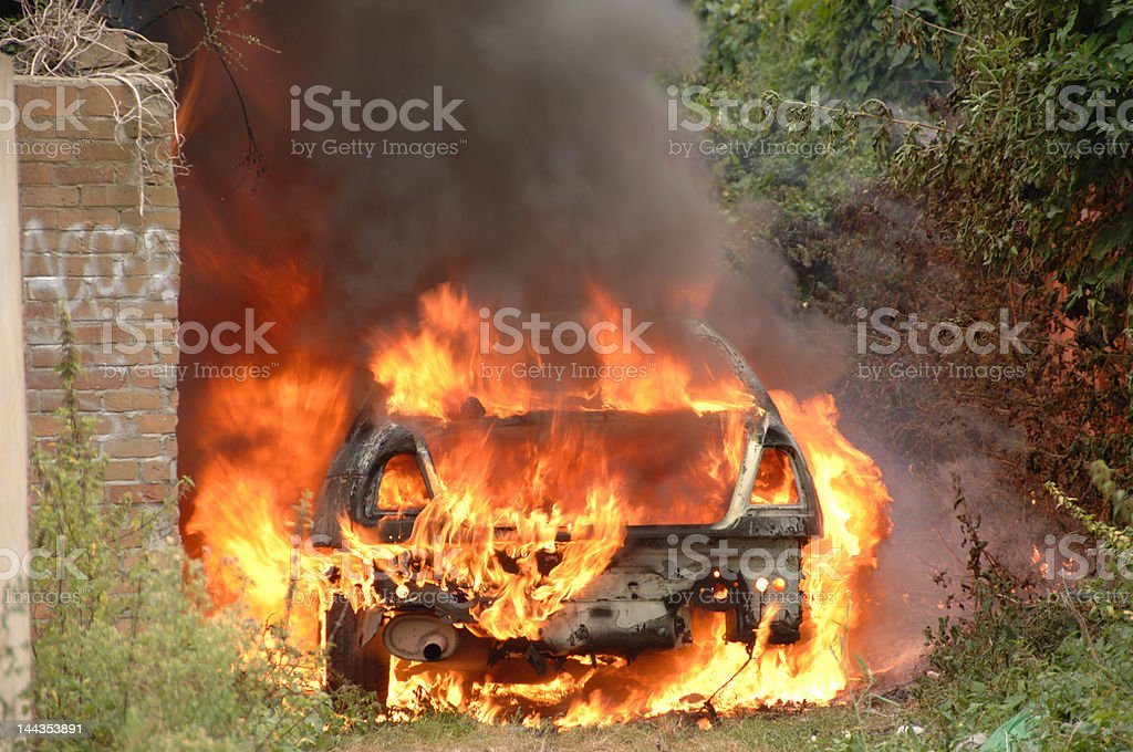 car on fire in alley way stock photo