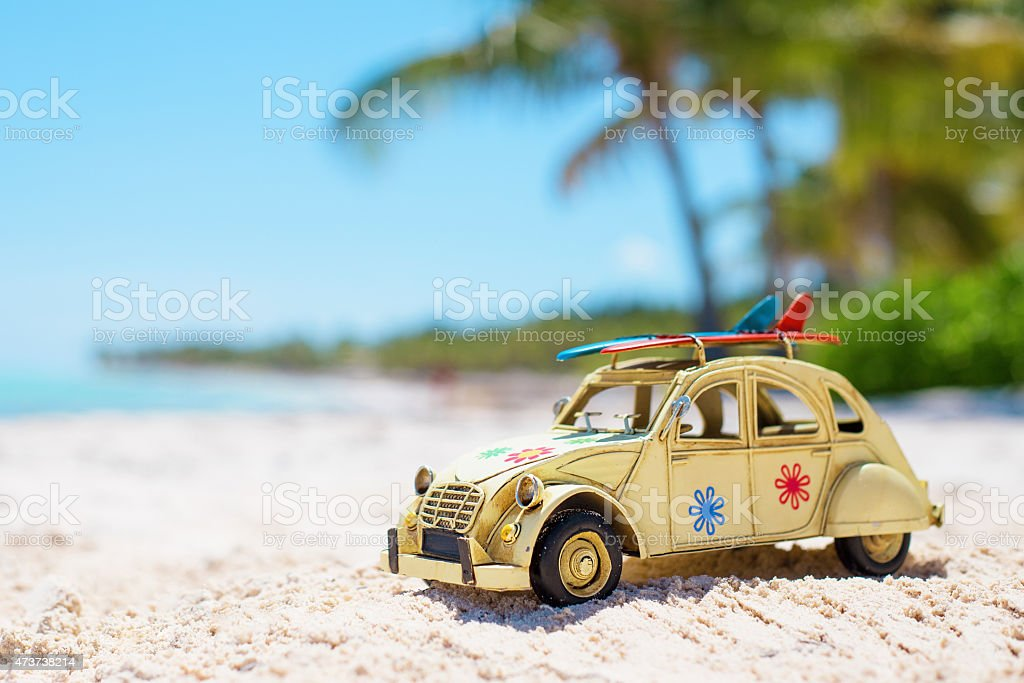 Car on the beach with surfboards on the roof stock photo