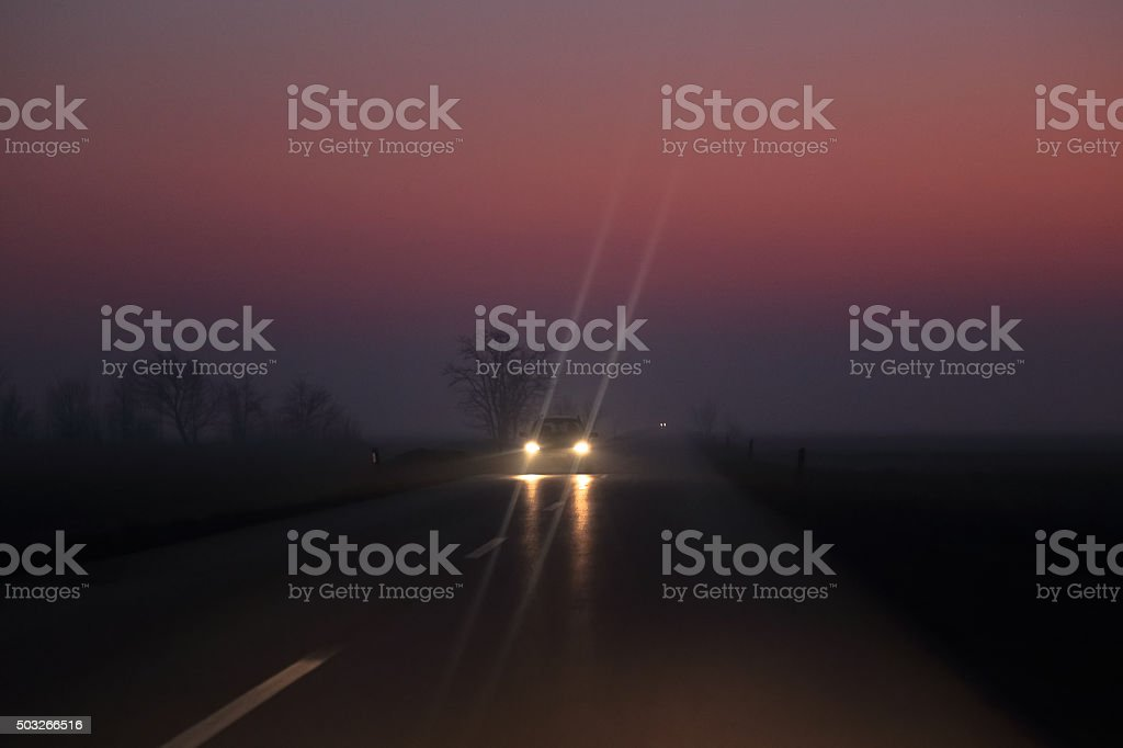 Car on the night road at the sunset stock photo