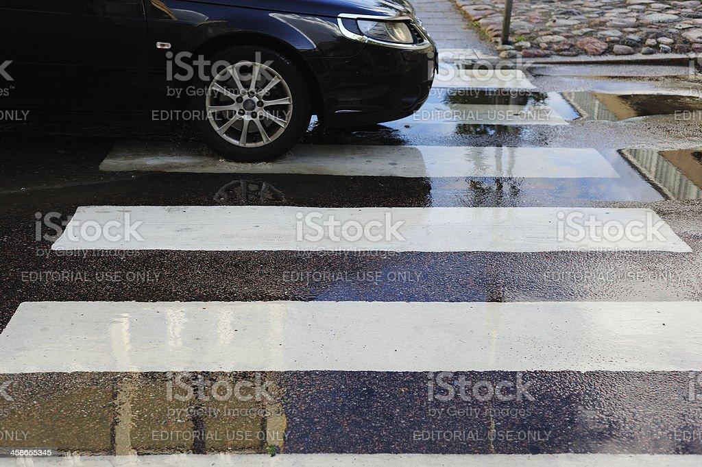 Car on zebra crossing, a rainy day, wet asphalt stock photo