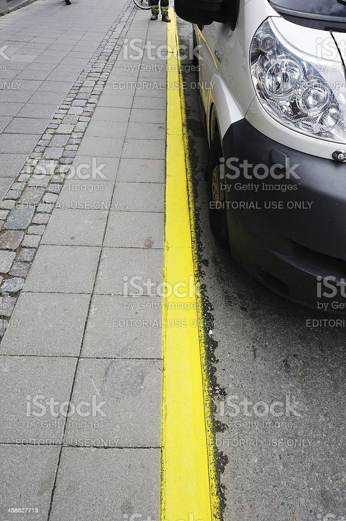 Car parked next to sidewalk with yellow line royalty-free stock photo
