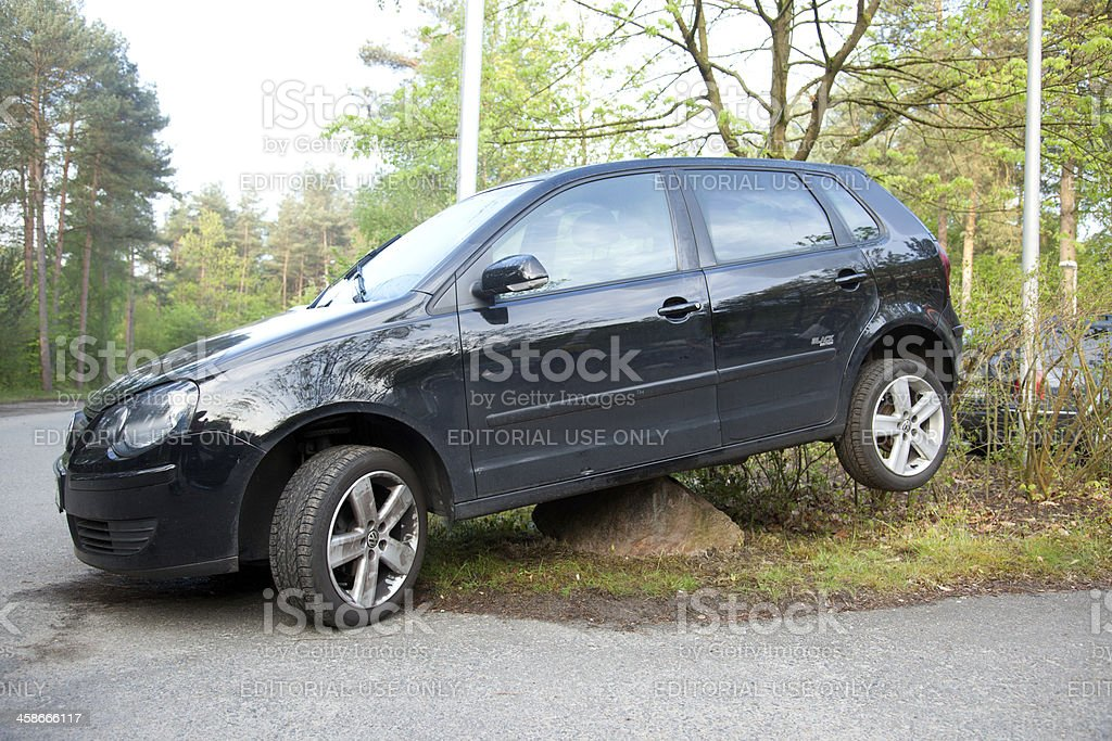 Car parked on a too big stone stock photo