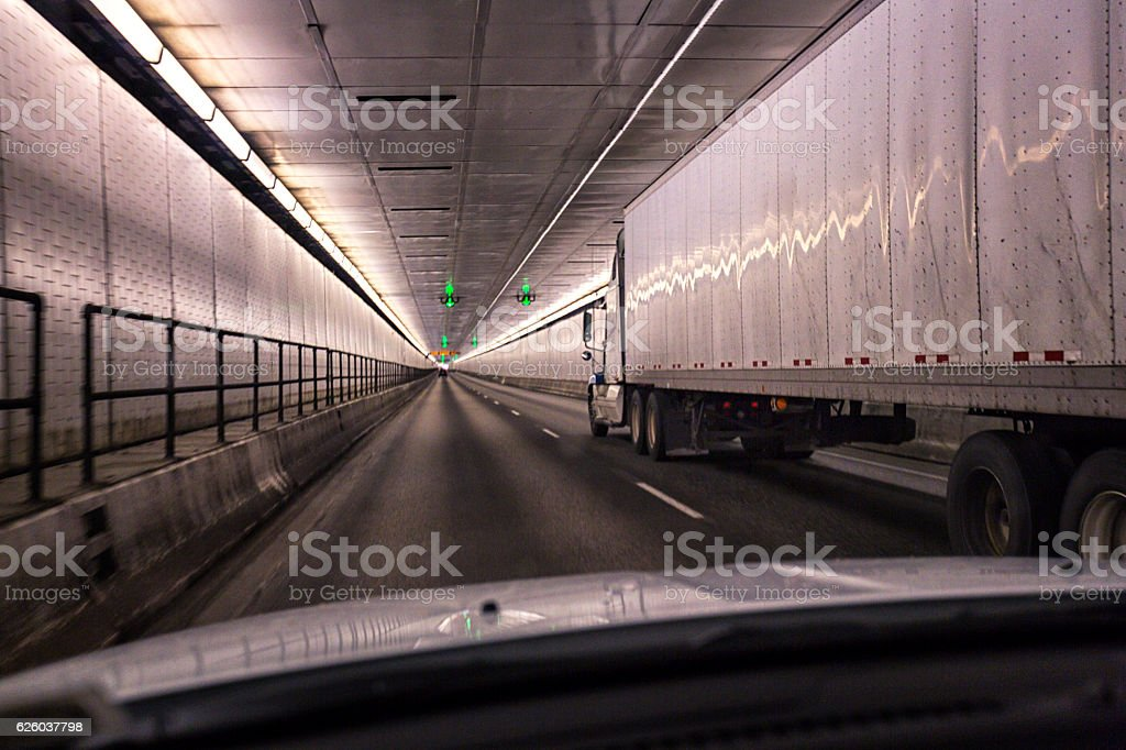Car Passing Trailer Truck Inside Pennsylvania Turnpike Lehigh Road Tunnel stock photo