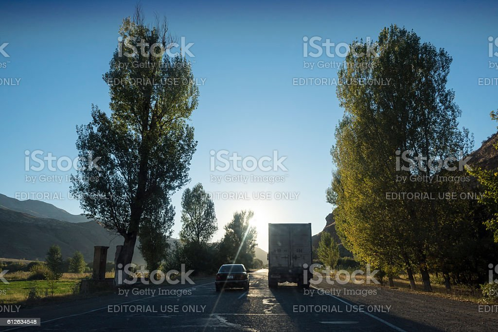 Car passing truck on highway in Armenia stock photo