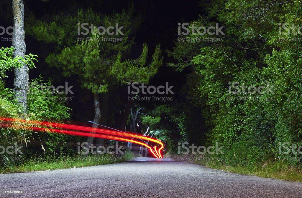 Car proceed into creepy street at night royalty-free stock photo