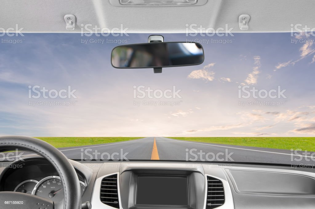 Car rear view mirror inside the car and drive to sunset. stock photo