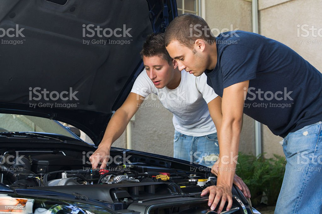 Car Repair and Engine Maintenance, Men Working Examining Under Hood stock photo