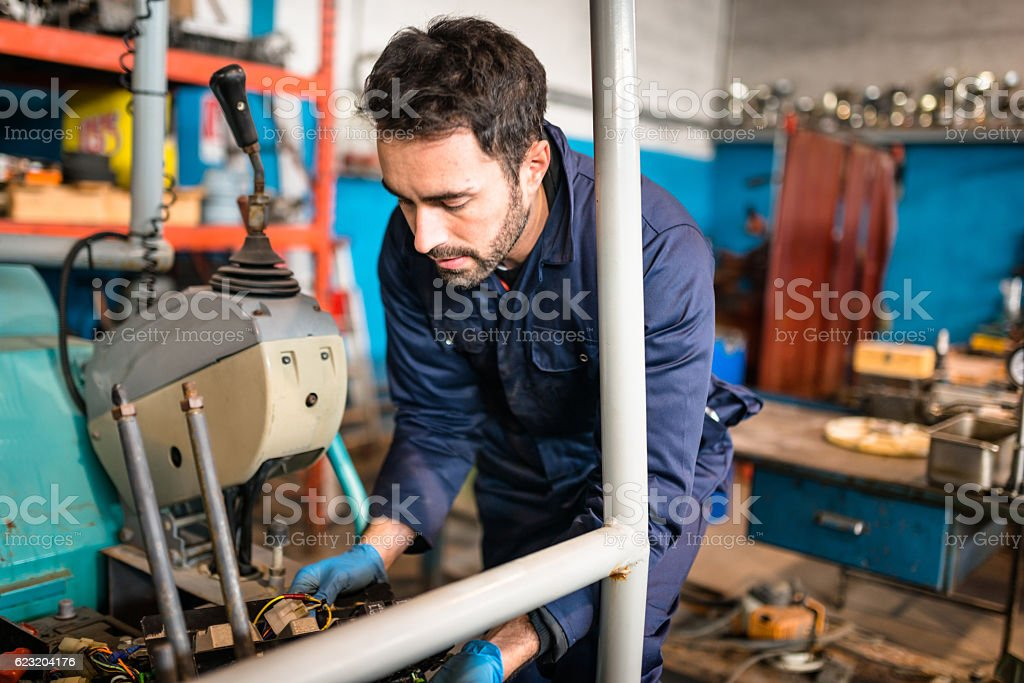 car repairman electrician fixing the truck engine on the garage stock photo