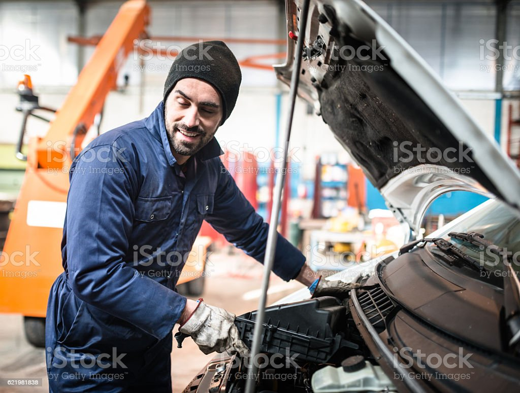 car repairman fixing the truck engine on the garage stock photo