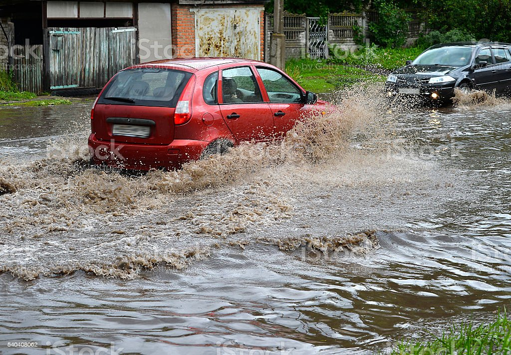 Car rides in heavy rain on a flooded road stock photo