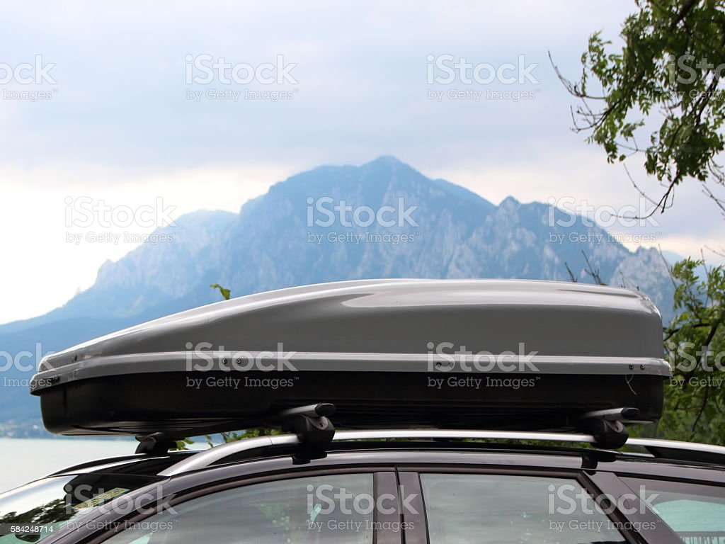 Car Rooftop Box with Mountain and Lake in Background stock photo