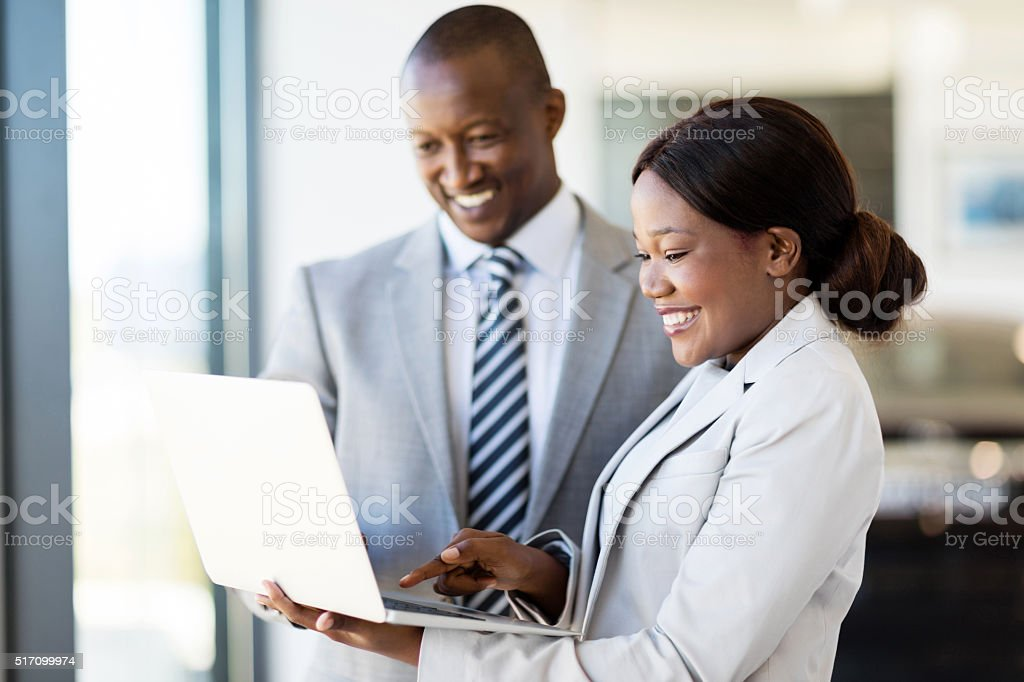 car sales consultants working on laptop computer stock photo