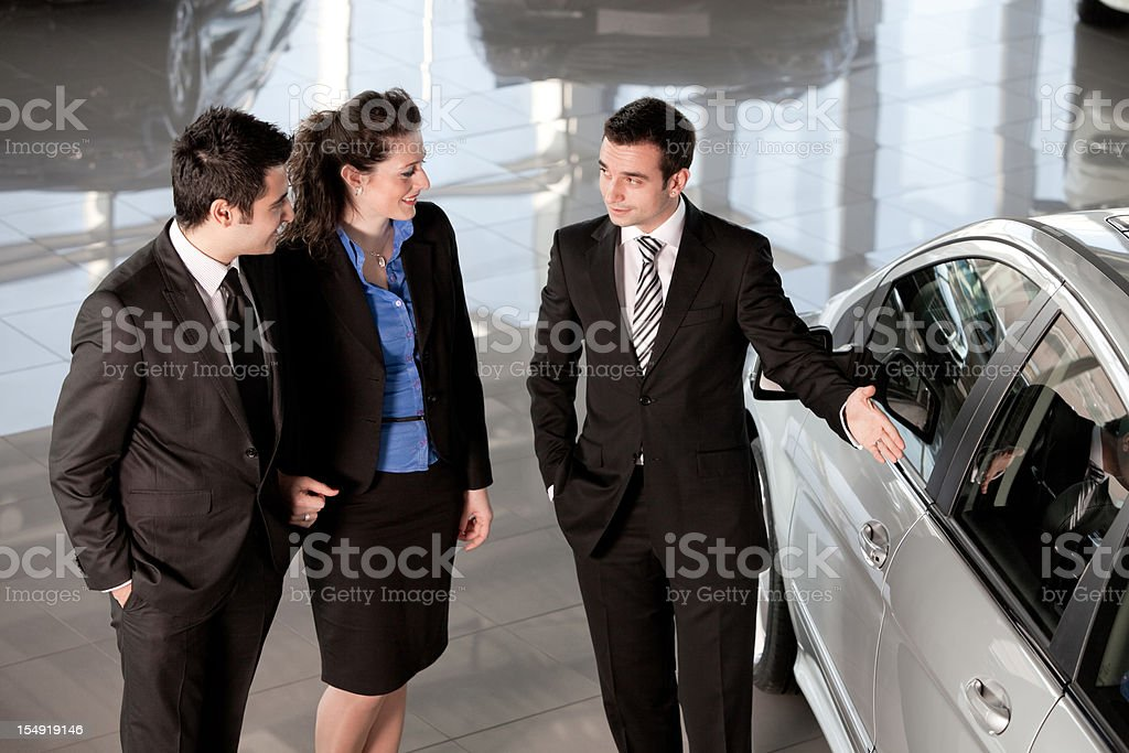 Car Salesman and Couple Buyer royalty-free stock photo