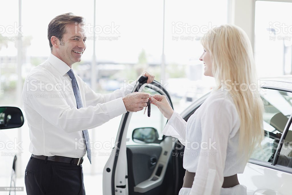 Car salesman handing keys to customer stock photo