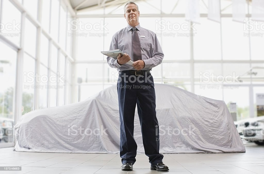 Car salesman standing in showroom royalty-free stock photo