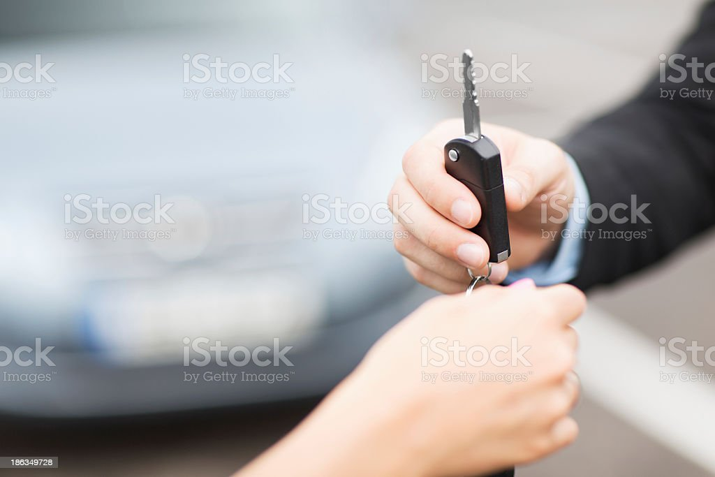 Car salesman's hand handing a large key to a customer's hand stock photo