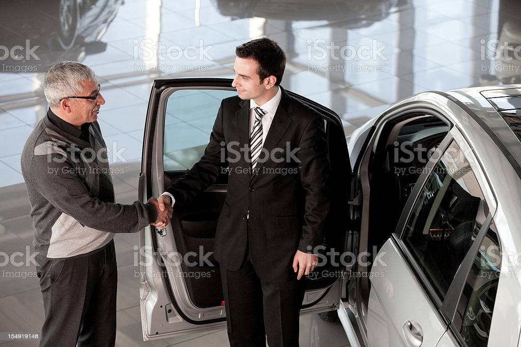Car salesperson and mature man royalty-free stock photo