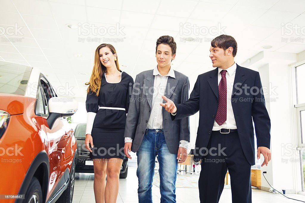 car salesperson showing customers a new SUV royalty-free stock photo