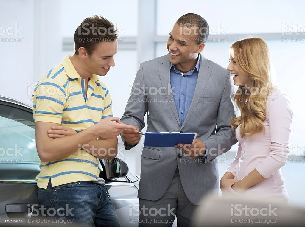 Car salesperson talking to his customers. stock photo
