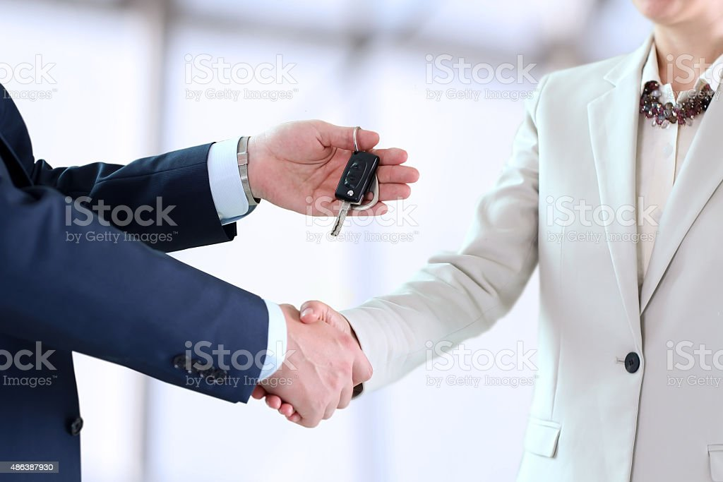 Car saleswoman handing over the keys for a new car stock photo