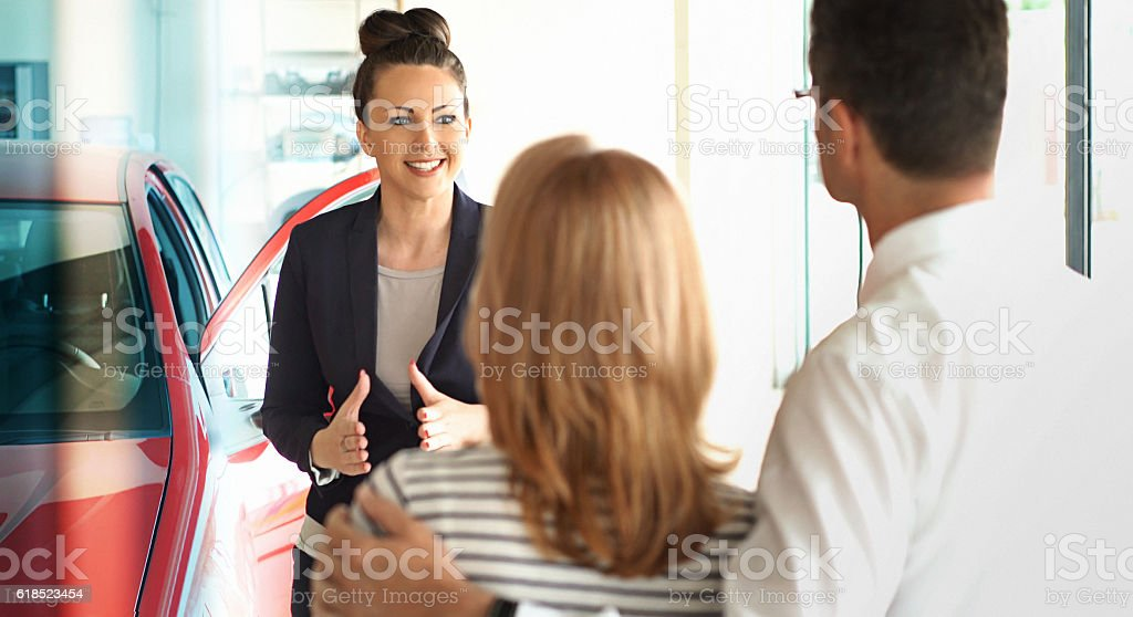 Car saleswoman trying to make a sale. stock photo