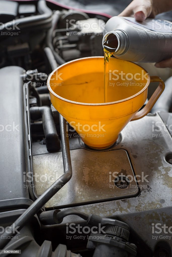 Car servicing mechanic pouring lubricant oil to engine. stock photo
