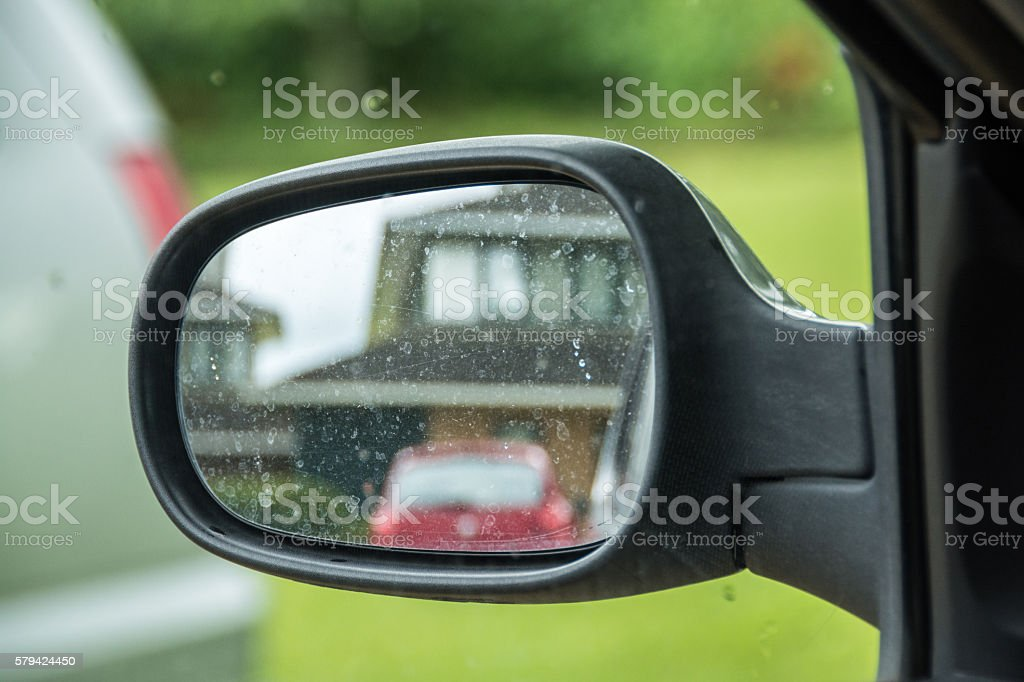 Car side rear-view mirror with house reflection stock photo
