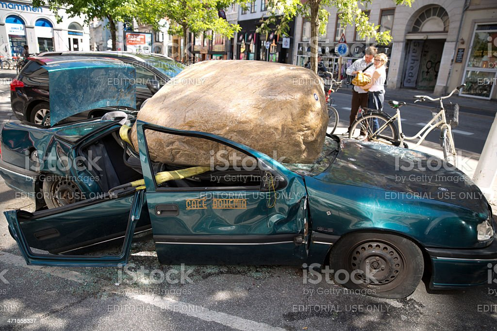 Car smashed by huge rock stock photo