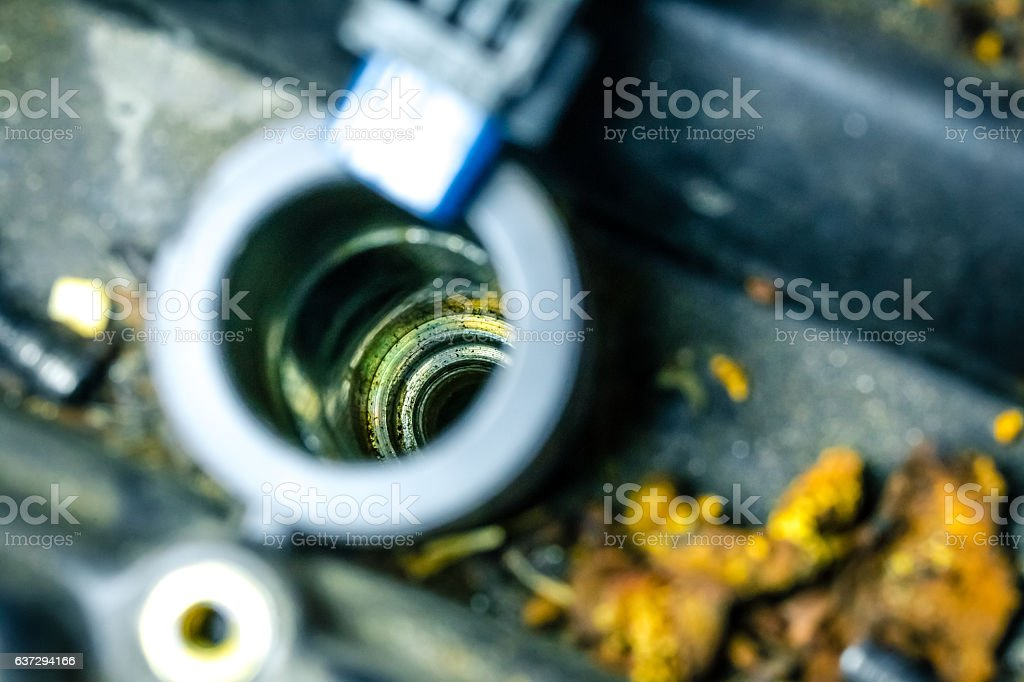 Car spark plug inside chamber on top of a piston stock photo
