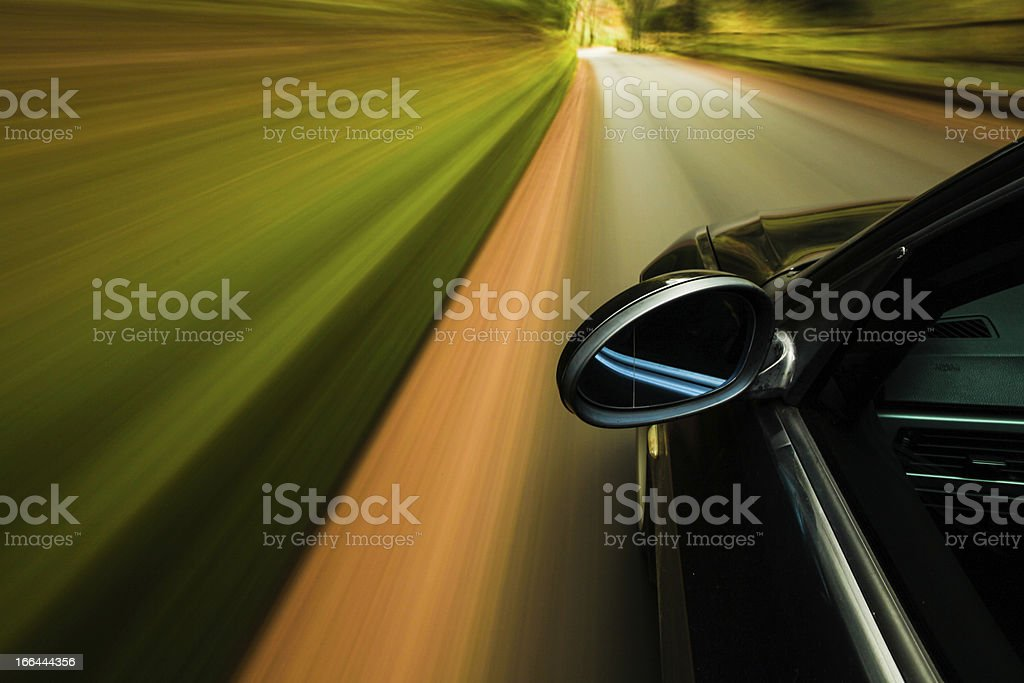 Car speeding on the road looking at side rear view mirror stock photo