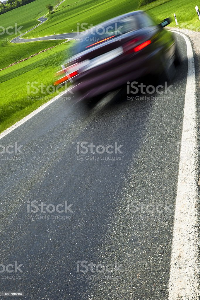 Car Speeding on Winding Country Road, Spring Landscape, Blurred Motion royalty-free stock photo