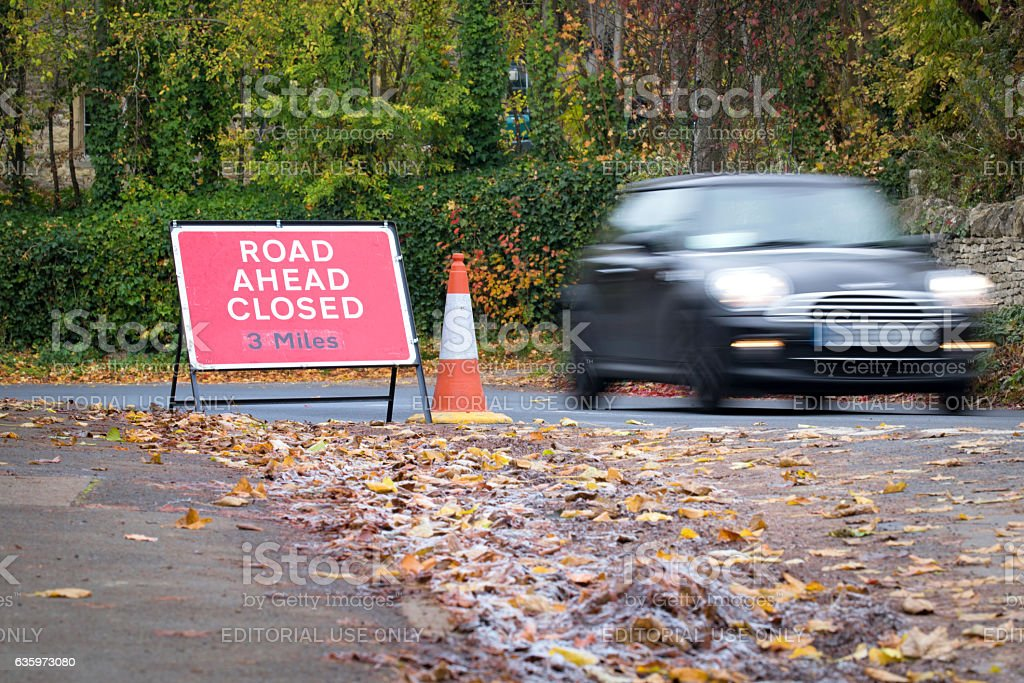 Car speeding past a 'Road ahead Closed' sign stock photo