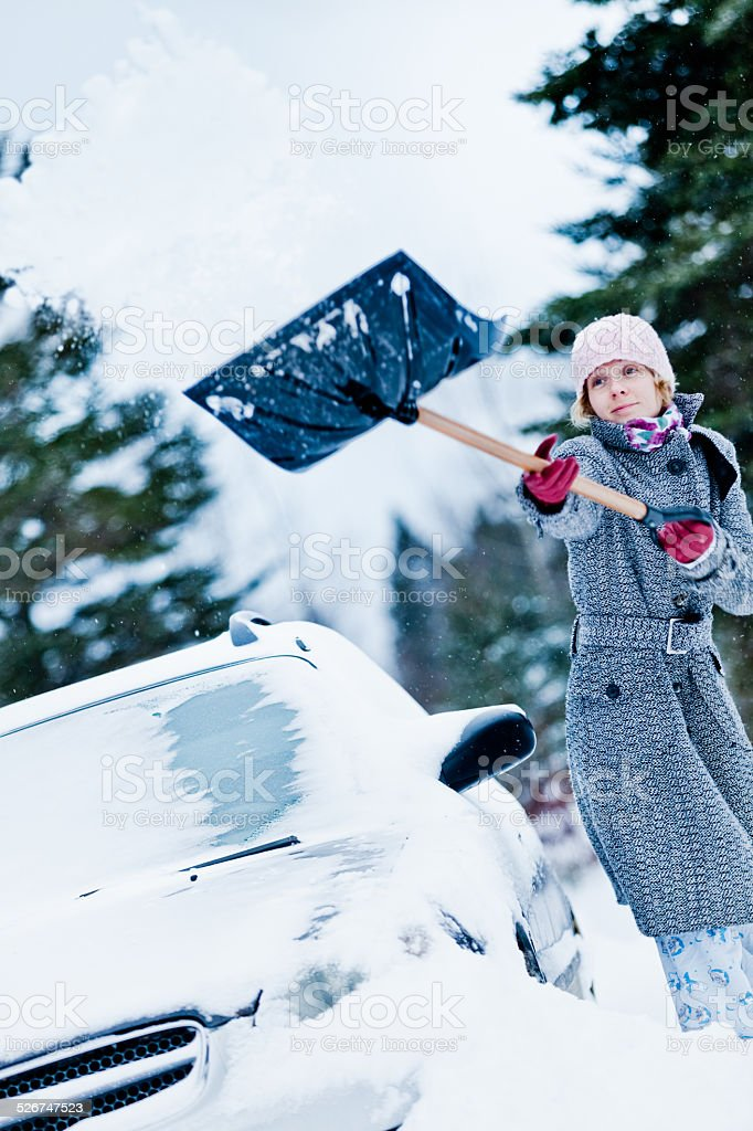 Car Stuck in the snow and a Woman Shoveling stock photo