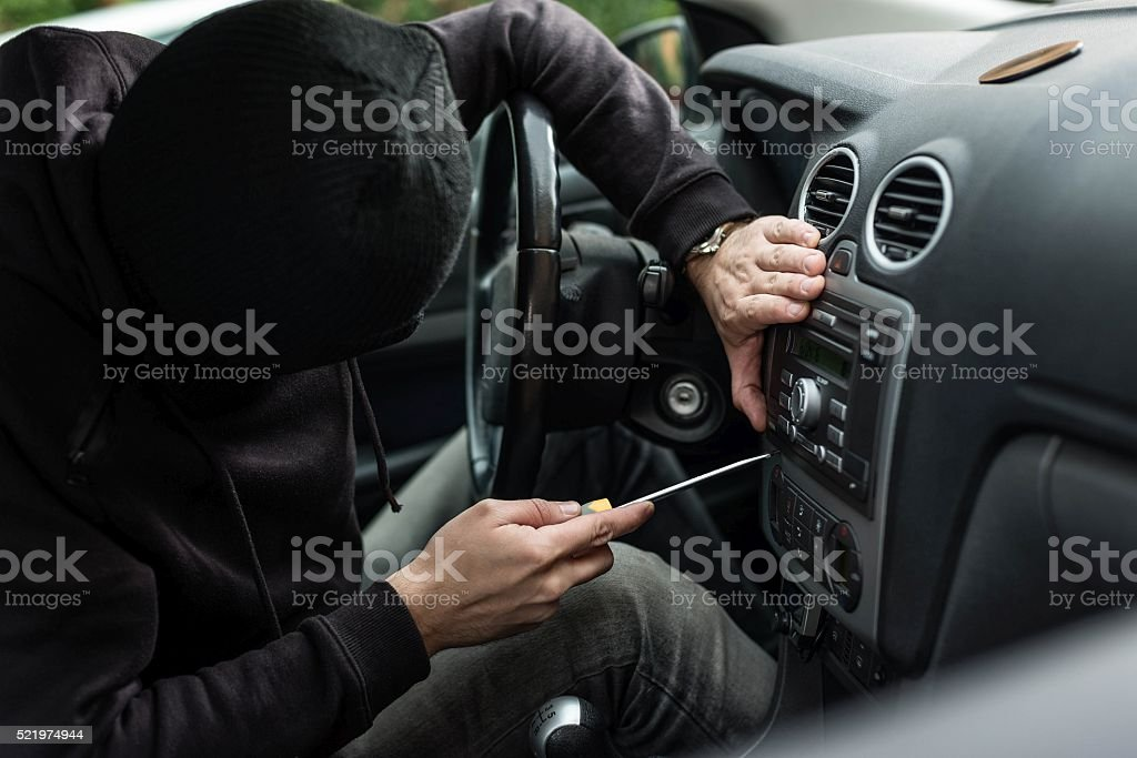 Car thief head trying to steal car radio stock photo