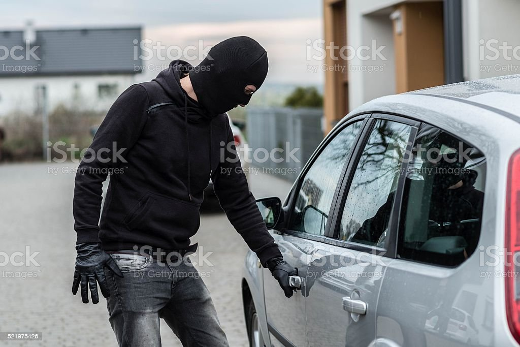 Car thief pulls the handle of a car. stock photo