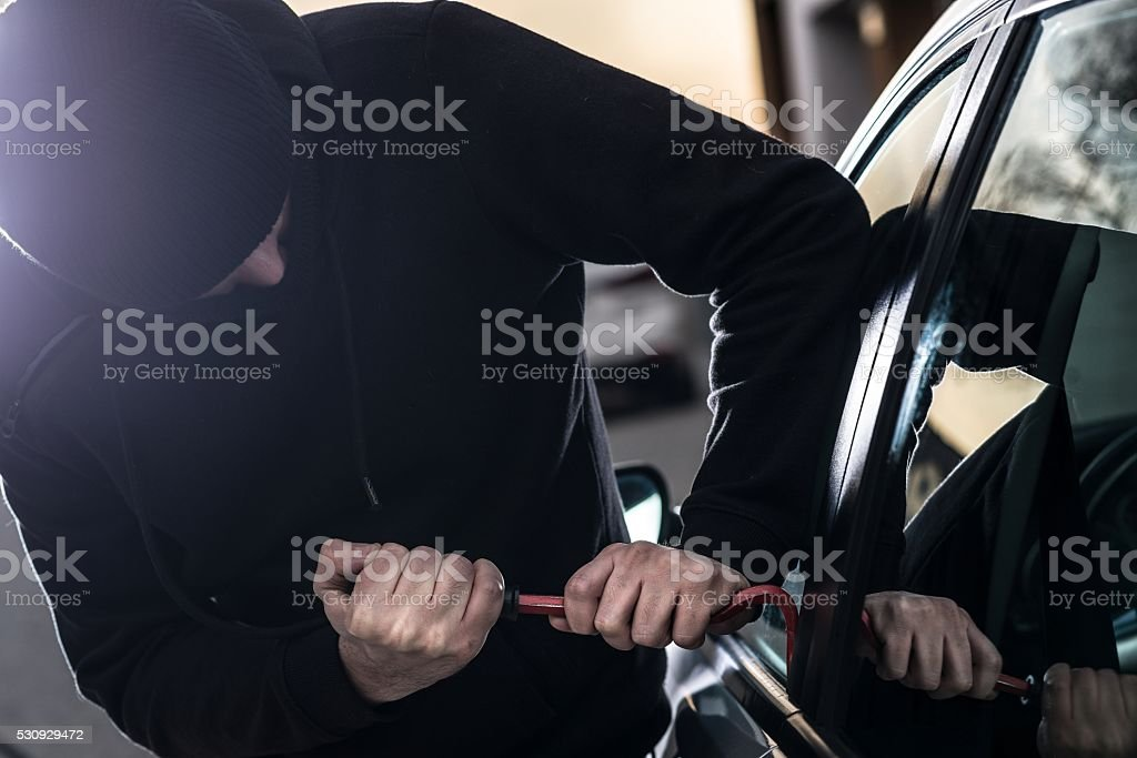 Car Thief tries to break into car with crowbar stock photo