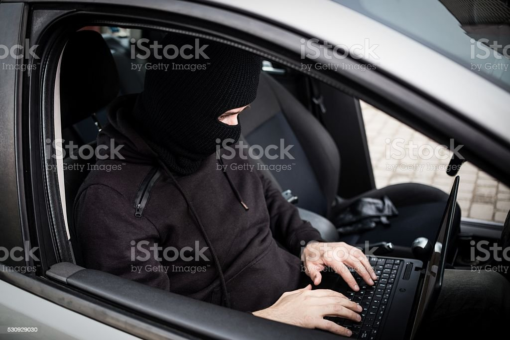 Car Thief tries to disarm car security systems stock photo