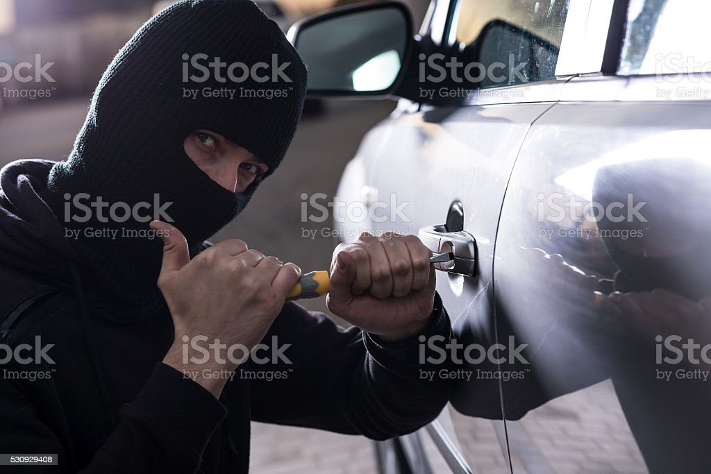 Car Thief tries to open car with screwdriver stock photo