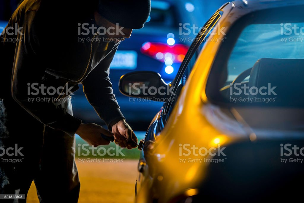 Car Thief Using a Screwdriver to Brake into a Car stock photo